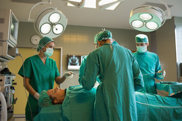 Group of surgeons working on a female patient