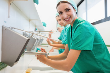 Surgeons washing their hands while smiling