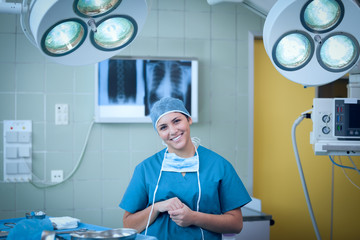 Smiling surgeon under surgical light