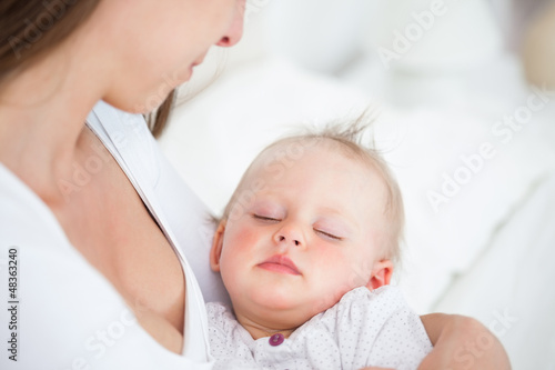 Baby falling asleep in the arms of her mother