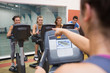 Instructor motivates happy people at spinning class