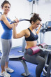 Female trainer with client on weights machine