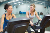 Two women working out on exercise bikes