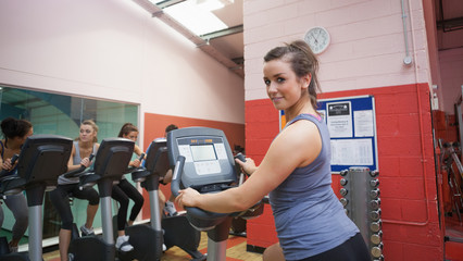 Happy woman teaches spinning class