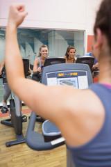 Motivational female instructor teaches spinning class