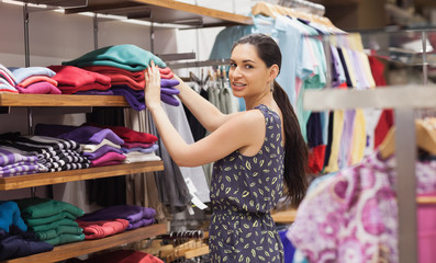 Woman putting jumpers on shelf