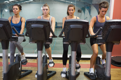 Four women working out at spinning class