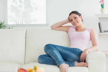 Woman sitting on the couch in a living room and relaxing