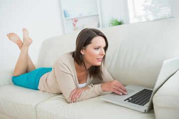 Brunette lying on sofa and using her laptop