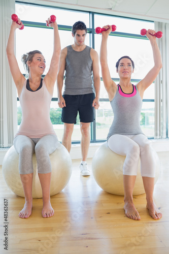 Two women at the gym with their coach