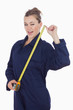 Female tecnician holding measuring tape as she winks