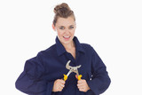 Playful female technician holding pliers wrench