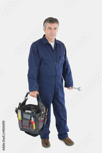 Portrait of mechanic carrying tool bag