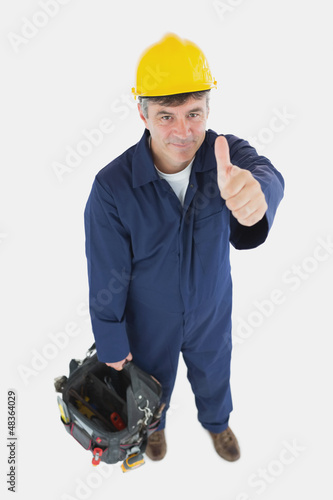 Technician with tool bag gesturing thumbs up
