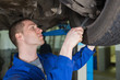Auto mechanic repairing car with spanner