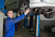 Auto mechanic adjusting car tire