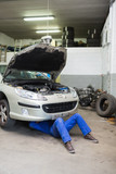 Auto mechanic working under car