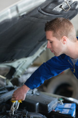 Car mechanic adjusting engine