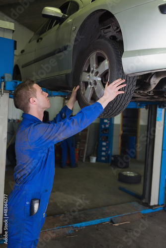 Male mechanic examining car tire