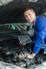 Happy mechanic with digital tablet