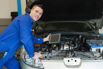 Mechanic by car holding digital tablet