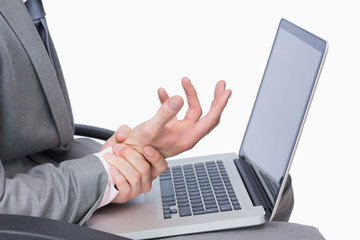 Business man with wrist pain while using laptop