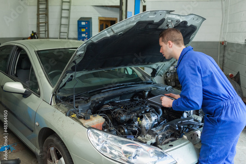 Mechanic analyzing car engine