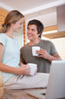 Couple looking at each with coffee cups while using laptop