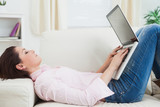 Casual woman lying on sofa and using laptop