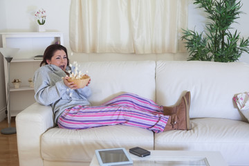 Scared woman throwing popcorn while watching film on couch