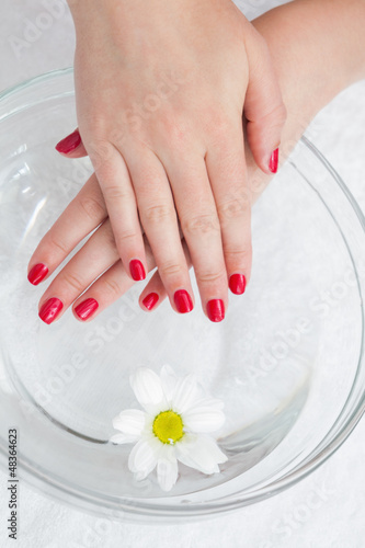 Red painted finger nails with flower in bowl