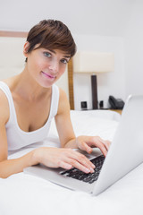 Pretty woman using laptop on bed