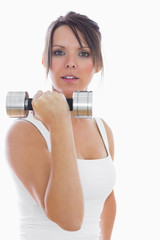 Portrait of young woman exercising with dumbbell