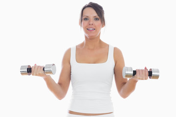 Portrait of young woman exercising with dumbbells