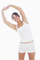 Portrait of smiling woman in sportswear holding hands up togethe