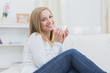 Smiling woman with coffee cup sitting on couch