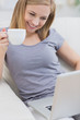 Smiling woman with coffee cup using laptop on sofa
