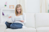 Casual young woman reading magazine at home