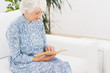 Elderly calm woman reading a old book