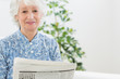 Elderly calm woman reading newspapers