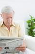 Elderly focused man reading newspapers