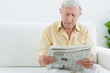 Elderly concentrated man reading newspapers