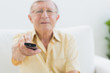Concentrated elderly man using the remote