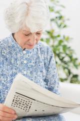 Elderly focused woman reading newspapers