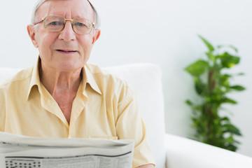 Cheerful elderly man reading the news