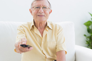 Smiling elderly man using the remote