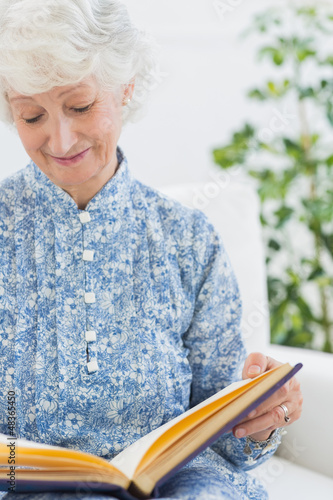 Elderly woman looking at her album