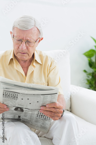 Focused elderly man reading the news