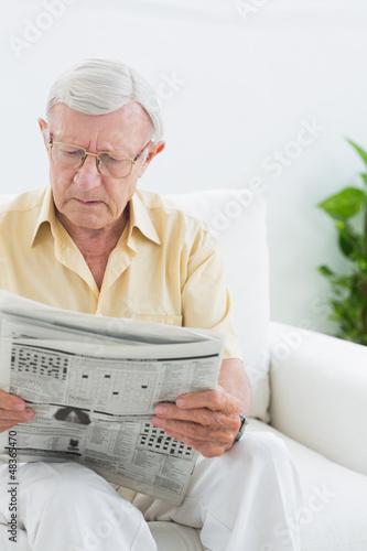 Focused elderly man reading the news