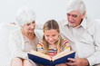 Granddaughter reading book with grandparents